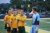 The boys' soccer team lines up for the calling of the player's names and the playing of the national anthem. Photo by Grace Allen.