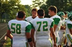 """Mason stands with teammates junior Seth Cook, senior Brett May, and senior Jake Quenichet as they talk with a coach after their play. """"My favorite thing about football is the connections you make through the years with friends and coaches,"""" said Quenichet. Photo by Grace Allen."""