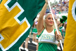 "Senior Makenna Moravec runs with the 'F' flag as others follow with 'C,' 'H,' and 'S' flags, marking FC's first touchdown. ""My favorite thing about cheering on the sidelines is when the crowd gets involved in the cheers and chants,"" said Moravec. Photo by Grace Allen."