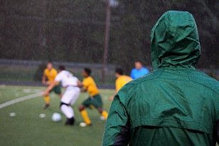 As the rain pours down, Coach Tim Rice watches the game from the sidelines. Photo by Grace Allen.