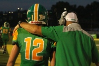 """Senior Bison Purtle is embraced by coach James Bragg after running a good play. """"I think of coach Bragg like a second dad and I feel like we're one big family,"""" said Purtle. Photo by Grace Allen."""