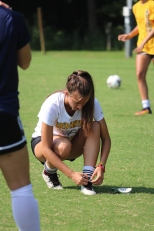"""Junior Spencer Freiberger ties her shoelaces during warm-ups for the girls green and gold soccer scrimmage.""""The warmups are basically what get us into the right mindset of the game. We get rid of any bad touches that we have on the ball with a series of passing drills and do a lot of dynamics in sync with each other to get motivated as a team,"""" said Freiberger. Photo by Brooke Miller."""