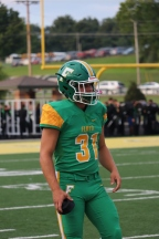 """Junior Cole Hussung watches his teammates play from the sidelines. """"My favorite part about a game is the opening kickoff to the game. That really gets your adrenaline pumping, especially if you are the first one to touch the ball,"""" said Hussung. Photo by Brooke Miller."""