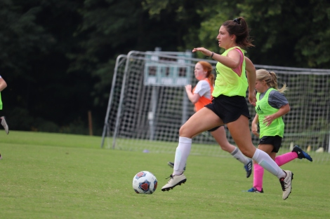Senior Renee Sisloff prepares to kick the moving soccer ball to another member of the green team. Photo by Brooke Miller.
