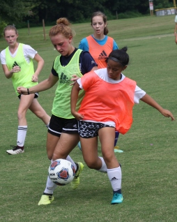 Junior Audrey Brumfield and freshman Linde Stockton go after the ball with teammates close behind for help during the second half of the girls' soccer scrimmage at FC on Aug 4. Photo by Nicholas Gordon.