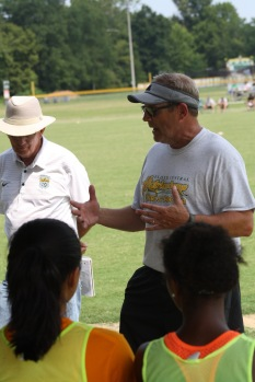"""Head coach Lewis Stevens talks to the girls about what they are doing right and wrong before the second half of the game gets started. """"When out there you will have to play to your best capability,"""" says Stevens. Photo by Nicholas Gordon."""