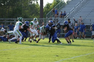 """Senior Tyler Edwards runs through the opposing player. """"I have been playing football ever since I could walk. Me and my dad would always go in the front yard and play catch,"""" said Edwards. Photo by Sophia Perigo."""
