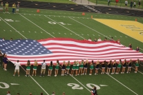 FC cheerleaders join the NJROTC unit to spread the American flag across the field during the marching band's performance of the national anthem. Providence students joined FC students in sporting the theme for the evening: America. Photo by Taylor Watt.