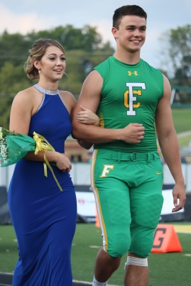 """Seniors Lauren Thompson and Brett May stroll arm in arm to their spot next to the other Homecoming candidates on the football field. """"My favorite part was getting all dressed up with the other girls and walking at the game,"""" said Thompson. Photo by Brooke Miller."""