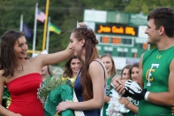 Former Homecoming Queen Delaney Mazza places the crown on the head of the 2018 homecoming queen, senior Riley Woodruff, while her escort, senior Jake Quenichet, claps for her along with the rest of the crowd and candidates. Photo by Brooke Miller.