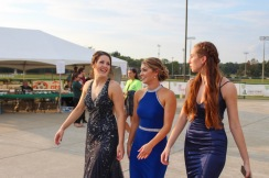 """Seniors Kamryn Plaiss, Lauren Thompson, and Riley Woodruff chat as they walk onto the field to join the Homecoming court of 2018. """"Having all of my friends on the Homecoming court made the night so much fun!"""" said Woodruff. Photo by Grace Allen."""