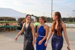 "Seniors Kamryn Plaiss, Lauren Thompson, and Riley Woodruff chat as they walk onto the field to join the Homecoming court of 2018. ""Having all of my friends on the Homecoming court made the night so much fun!"" said Woodruff. Photo by Grace Allen."