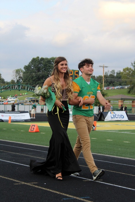 Senior Olivia Fonton is escorted by senior Lucas Mosier as they walk to join the other representatives. Photo by Grace Allen.
