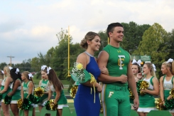 """Senior Lauren Thompson smiles with her escort senior Brett May as they pose for a photo by the parents and photographers. """"I was pleasantly surprised when I found out I was voted on to the court. I had so much fun with my escort and the other girls,"""" said Thompson. Photo by Grace Allen."""