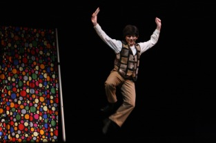 """Charlie Bucket, played by junior Isabella Arnett, jumps for joy after finding the last golden ticket. """"I can't wait to go to all the different elementary schools and perform for my old teachers and to see how the kids react to the show,"""" said Arnett. Photo by Sophia Perigo."""