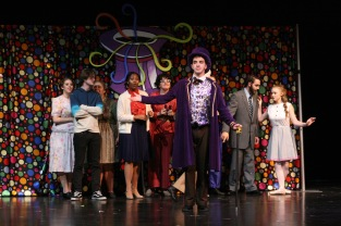 """Willy Wonka, played by senior Noah Hankins, stands in front of all the ticket winners before going on the tour of the factory. """"When I'm Performing on stage I feel happy that I am inspiring others,"""" said Hankins. Photo by Sophia Perigo."""