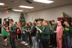 On Tuesday night, senior Alex Voyles and sophomore Autumn Meadows lead the other NJROTC cadets in singing Christmas carols to a group of senior citizens at Riverview Towers in downtown New Albany. Photo by Aurora Robinson.