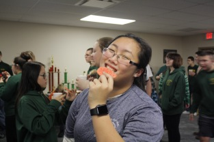 Sophomore Diem Tran smiles with her sugar cookie as everyone chats, spends time with each other, and participates in holiday themed games. Photo by Aurora Robinson.