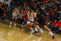 Senior Cobie Barnes dribbles around a New Albany guard as he drives towards the goal. Photo by Grace Allen.