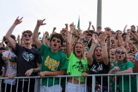 Seniors Grant Gibson, Garrett Grubbs, and Hope Wheatley lead the Floyd Central Student Section in cheers as they root for their football team. Photo by Grace Allen.