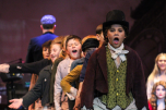 Fifth grader Zander Essex, joined by the orphan ensemble of Oliver!, dance and sing during a run of the show. Photo by Mary Ficker.