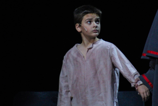 Oliver, fourth grader Lincoln Fogarty stands and watches his fellow cast mates sing. Photo by Mary Ficker.