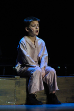 Fourth grader Lincoln Fogarty, who plays Oliver, sits on a bench and sings during a run of the show. Photo by Mary Ficker.