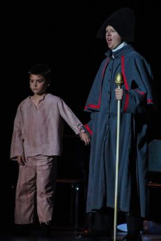 Senior Taylor Lockhart stands and sings while holding fourth grader Lincoln Fogarty's hand during a run of FC Theatre Arts production of Oliver! Photo by Mary Ficker.