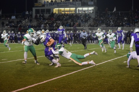 Junior Colin Cummins dives to stop the offense from gaining yards. Photo by Kate Zuverink.