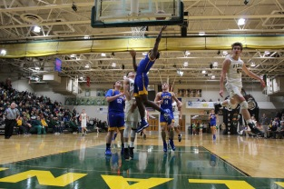 Senior Seth Burks avoids a foul as the Knights attempt to make a basket. Photo by Kate Zuverink.
