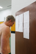 Dalton Lawver intently reads the heat sheets posted in the pool area so he knows what he's signed up to swim in the next meet. Photo by Grace Allen.