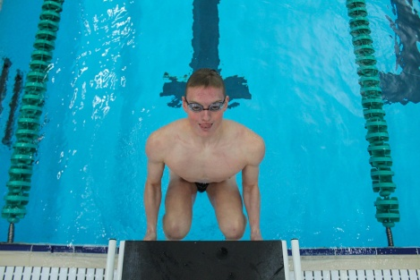 "Dalton Lawver focuses his eyes on the block as he readies himself in a backstroke start position. ""I am trying to break the 100 [- meter] backstroke record this year so I needed to keep swimming,"" said Lawver when asked why he decided to swim again this year. Photo by Grace Allen."