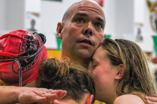 Head Swim Coach Joe Perkins hugs three of his swimmers after they win their relay race. Photo by Brock Kennedy.