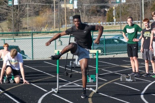 Junior Wenkers Wright lands on the ground after hurdling a hurdle in practice. Photo by Grace Allen.